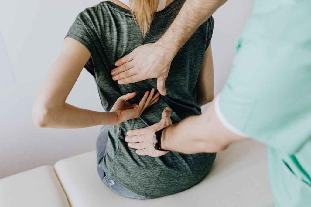 Patient indicating area of low back pain to therapist